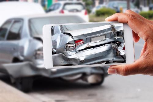 A person taking a photo of the damage to their car after an accident.