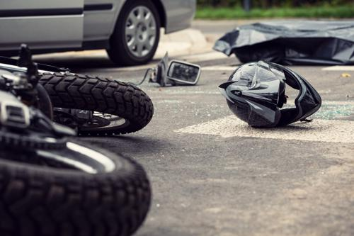 A motorcycle and helmet lying in the middle of a road after being hit by a car in Orange County.