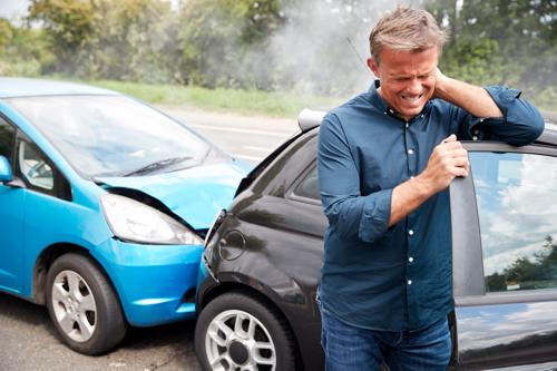 A man holding his injured neck after being rear-ended.