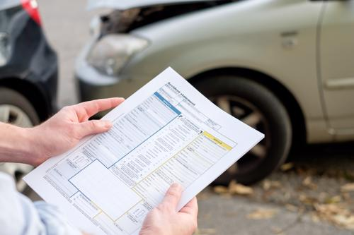 An insurance adjuster reviewing damage after a car accident.