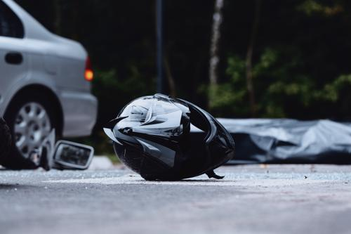 A helmet lying on asphalt with a car in the background.
