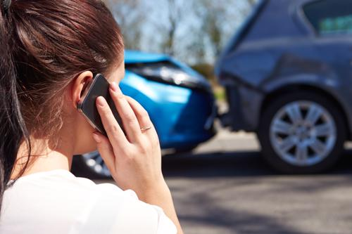 A woman calling an attorney after a rear-end car accident in Orange County.