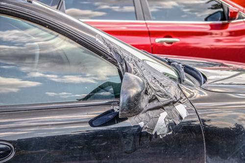 A car with paint and body damage after being sideswiped in Orange County.