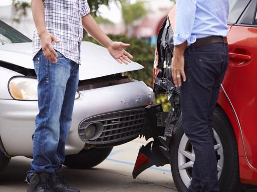 Two drivers in Santa Ana exchanging information after a car accident.