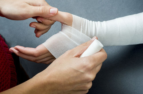 Close up of doctor bandaging a hand