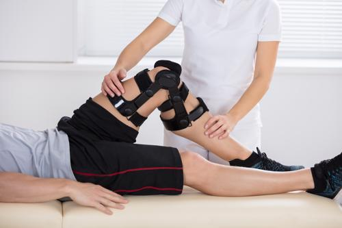 Man getting physical therapy for knee injury from slip and fall