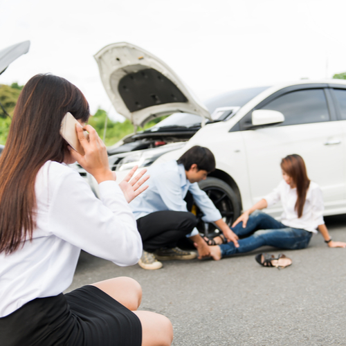 This is an image of a woman calling an Indio car accident lawyer at the scene of a crash with another hurt woman