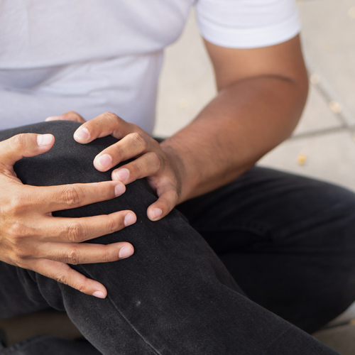 This is an image of a man who is holding his injured knee while sitting on the ground.