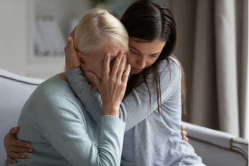 Young woman hugs crying elderly woman, Yucca Valley wrongful death lawyer concept