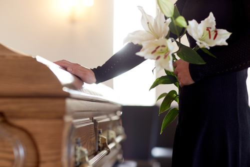This is an image of a woman holding flowers with hand on coffin of loved one